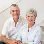 Senior couple sitting on stairs smiling at camera — Stock Photo #42920957