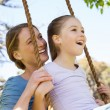 Happy mother swinging daughter at park — Stock Photo #42920971
