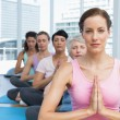 Class sitting with joined hands in a row at yoga class — Stock Photo #42921193