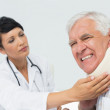 Female doctor examining a senior patients neck — Stock Photo #42921275