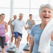 Senior woman gesturing thumbs up with people exercising — Stock Photo #42921615