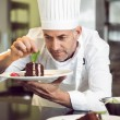 Concentrated male pastry chef decorating dessert in kitchen — Stock Photo #42922053