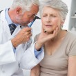 Male doctor examining senior patient's ear — Stock Photo