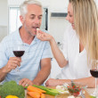Affectionate couple preparing dinner together and drinking red wine — Stock Photo #42922403
