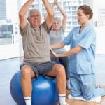 Female therapist assisting senior couple with exercises — Stock Photo