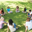 Friends sitting in a circle at park — Foto Stock #42922557