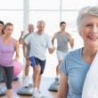Senior woman with people exercising in fitness studio — Stock Photo