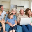 Family using laptop in living room — Stock Photo #42923229