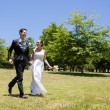 Bride and groom holding hands in park — Stock Photo