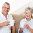 Senior couple sitting on couch drinking coffee smiling at camera — Stock Photo #42923965