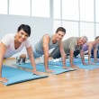 Group doing push ups in row at yoga class — Stock Photo #42924127