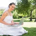 Bride using laptop in garden — Stock Photo #42924151