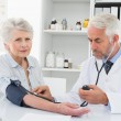 Doctor taking blood pressure of his retired patient — Stock Photo