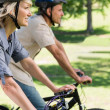 Couple riding bicycles in a park — Stock Photo #42924465