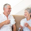 Senior couple sitting on couch drinking coffee — Stock Photo #42925931