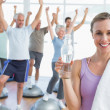 Woman holding bottle with people stretching hands at fitness studio — Стоковое фото