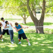 Woman playing tug of war with friends — Stock Photo #42926877