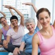 Trainer with women in row stretching hands at yoga class — Stock Photo #42927135