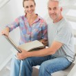 Happy couple picking out carpet samples together — Stock Photo