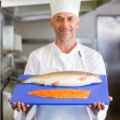 Confidence chef holding tray of raw fish in kitchen — Stock Photo