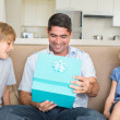 Father opening gift given by children — Stock Photo #42927741