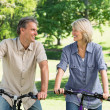 Couple riding bicycles in park — Stock Photo #42927789