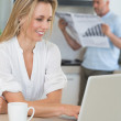 Smiling woman using laptop with partner standing with the paper — Stock Photo
