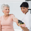 Female doctor fixing wrist brace on senior patients hand — Stock Photo #42927833