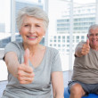 Senior couple gesturing thumbs up at medical gym — Stock Photo #42928023