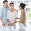 Interior designer showing colour wheel to happy young clients — Stockfoto