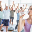 Woman drinking water with people stretching hands at fitness studio — Stock Photo