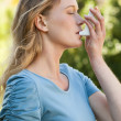 Young woman using asthma inhaler at park — Stock Photo
