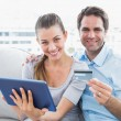 Happy couple sitting on the couch shopping online with tablet pc — Stock Photo