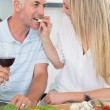 Affectionate couple preparing dinner together and drinking red wine — Stock Photo #42929347