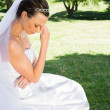 Bride sitting on grass in park — Stock Photo
