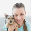 Smiling woman holding her yorkshire terrier puppy — Stock Photo #42929489