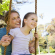 Happy mother swinging daughter at park — Stock Photo #42929547