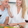 Affectionate couple preparing dinner together and drinking red wine — Stock Photo #42929655