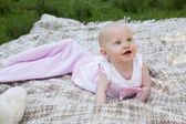 Cute baby lying on blanket at the park — Stock Photo