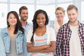 Young team of designers standing and smiling at camera — Stock Photo