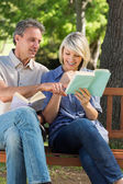 Couple reading books on bench — Stock Photo