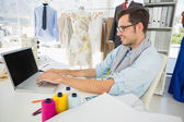 Concentrated young male fashion designer using laptop — Stock Photo