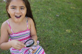 Girl examining a butterfly with magnifying glass at park — Stock Photo