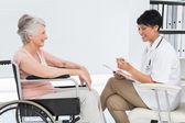 Arts in gesprek met een hogere patiënt in rolstoel — Stockfoto