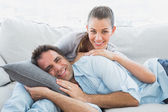 Cheerful couple relaxing on their sofa smiling at camera — Stock Photo