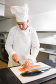 Concentrated male chef cutting fish in kitchen — Stock Photo