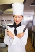 Cook holding knives in kitchen — Stock Photo