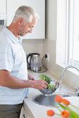 Casual man rinsing broccoli in colander — Stock Photo