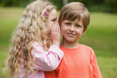 Girl whispering secret into boy's ear — Stock Photo