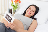 Pregnant woman holding sonography report — Stock Photo
